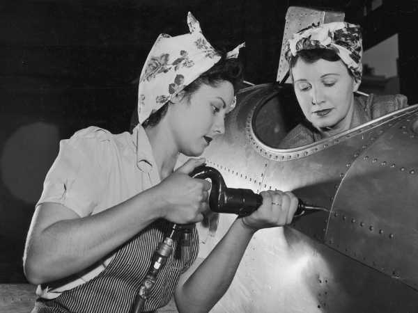 Women working to rivet the body of an airplane. Photograph by Harold Lambert.